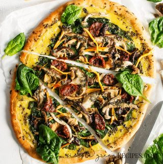 Gluten-free Vegan Pizza with vegan cheese, spinach, mushrooms and pesto