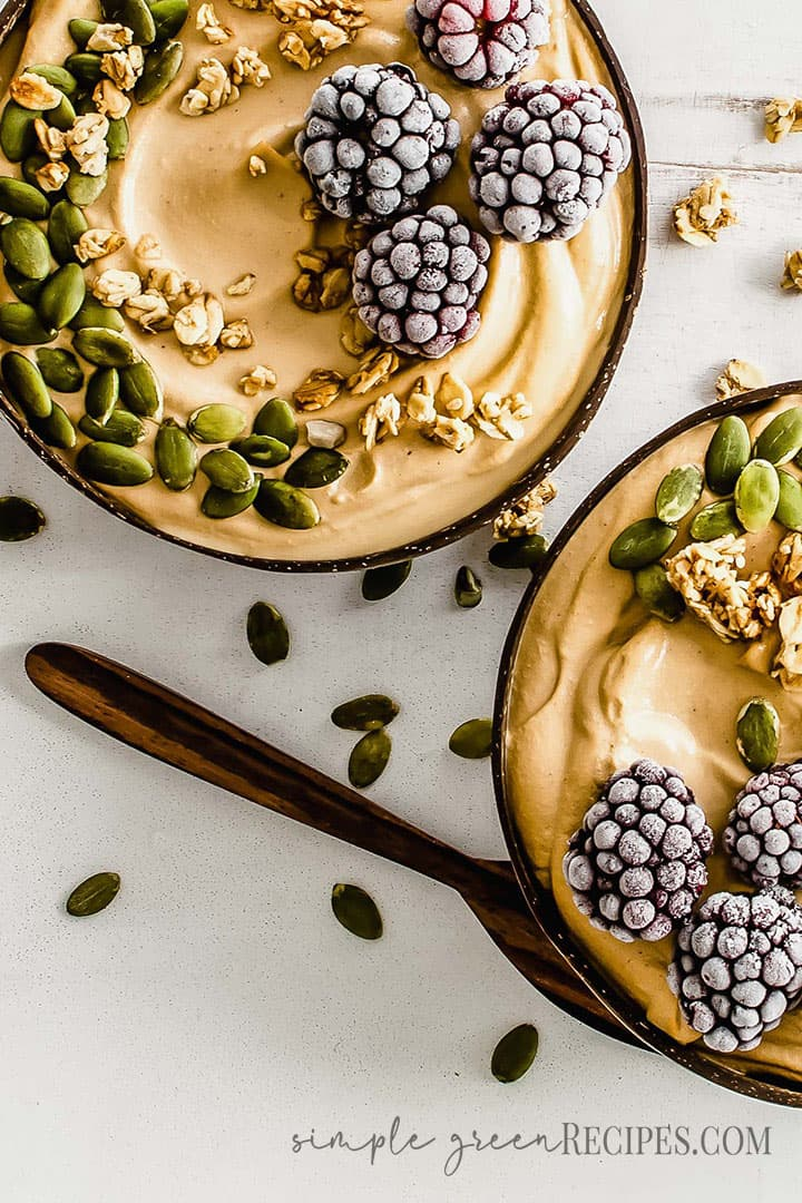 Overhead shoot of the Peanut Butter and Banana Smoothie topped with pumpkin seeds and frozen berries. Two bowls.