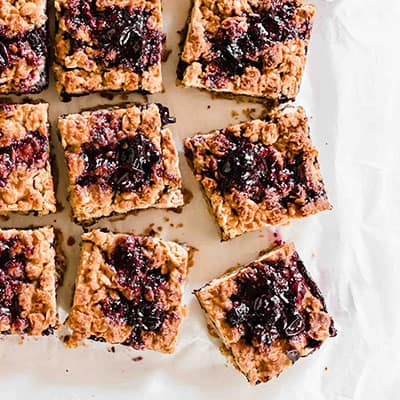 Close up of the Vegan Blueberry Oatmeal Bars sliced sliced and topped with blueberry compote.