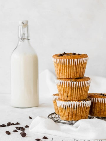 Close up of the Vegan Pumpkin Chocolate Chip Muffins stacked next to a bottle of milk.