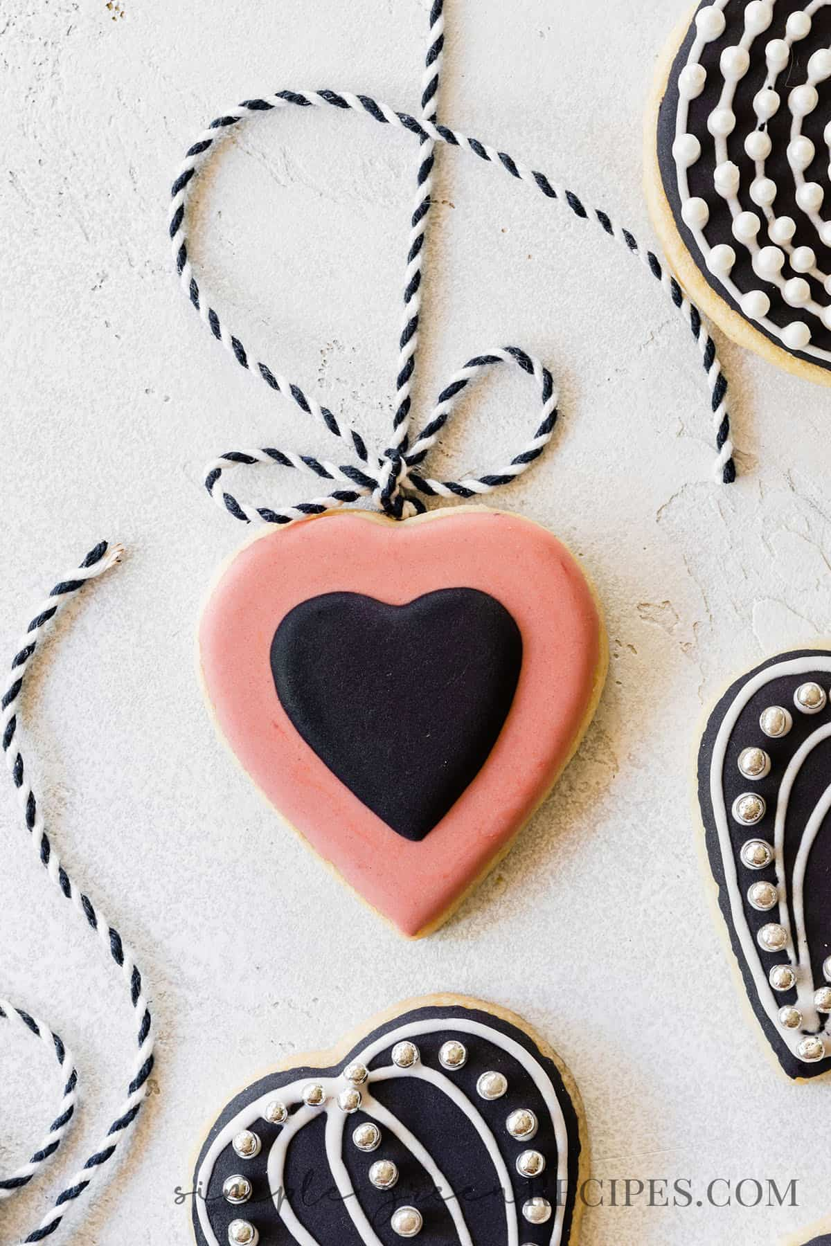 heart shaped sugar cookie decorated with pink and black royal icing, tied to a black and white string.
