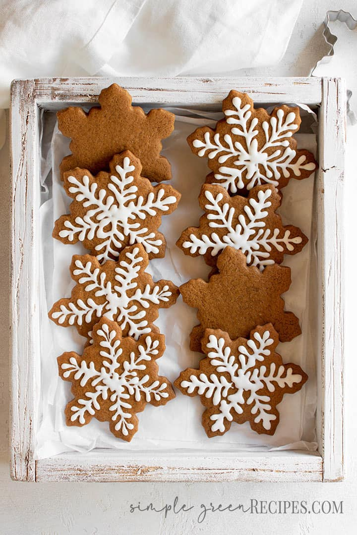 Over head shot of the decorated star shaped cookies in a wooden tray.