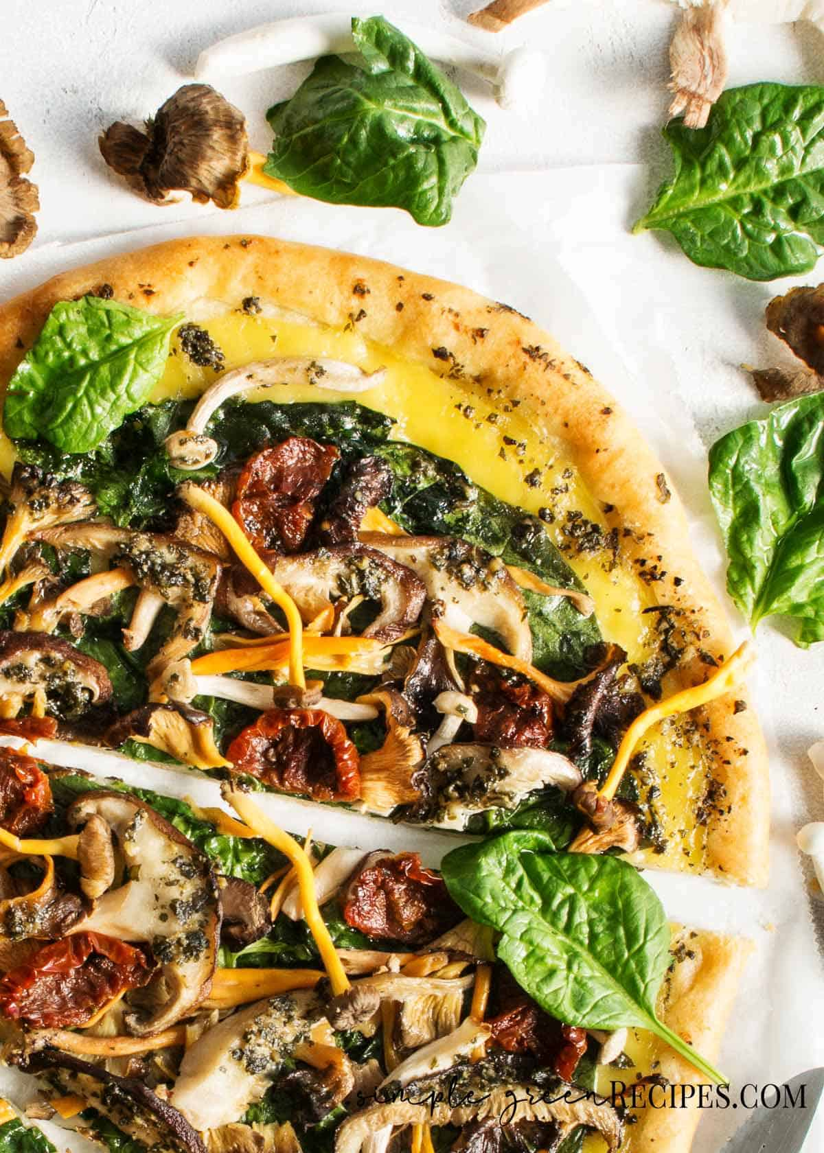 Sliced pizza topped with cheese and veggies and mushrooms against a white background.