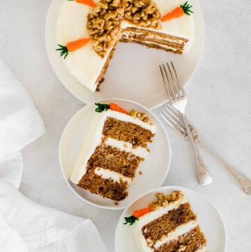 Sliced carrot cake on a white plate and two slices on two smaller white plates.