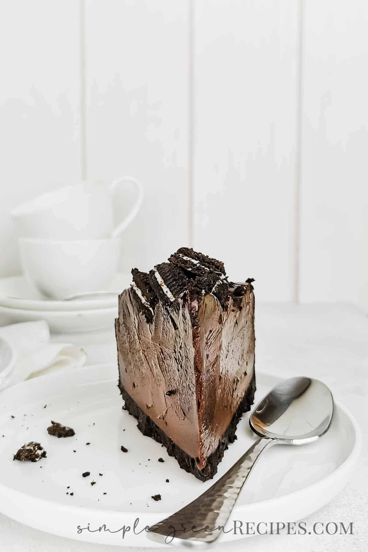 Slice of chocolate cheesecake topped with cookies, on a white plate and next to a silver teaspoon.