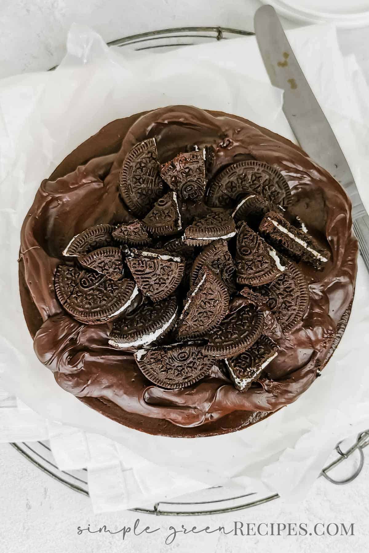 Uncut cheesecake made up of a cookie crust, chocolate cheesecake and topped with ganache and extra cookies.
