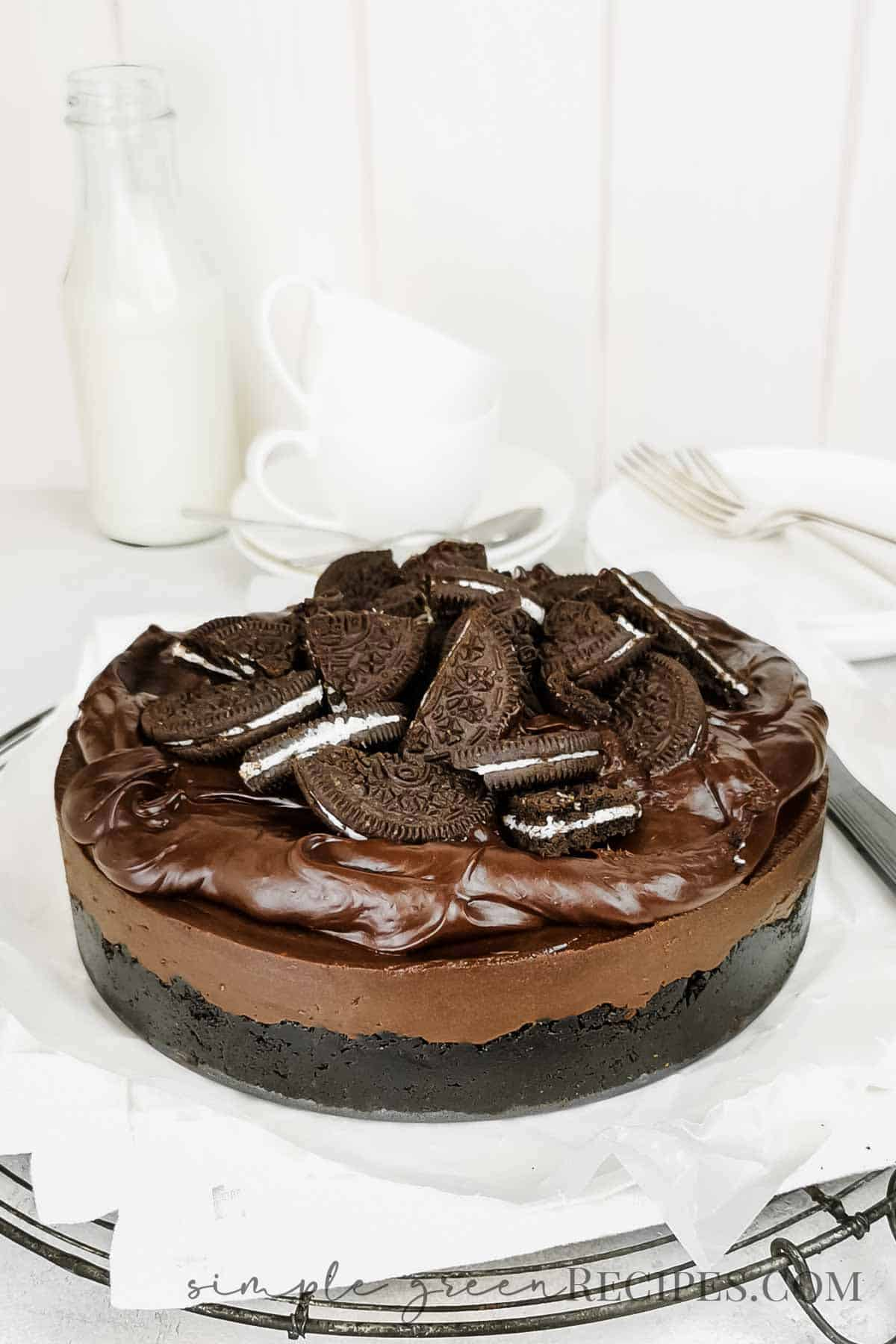 Uncut chocolate cheesecake topped with chocolate ganache and oreo cookies, on a wire rack.