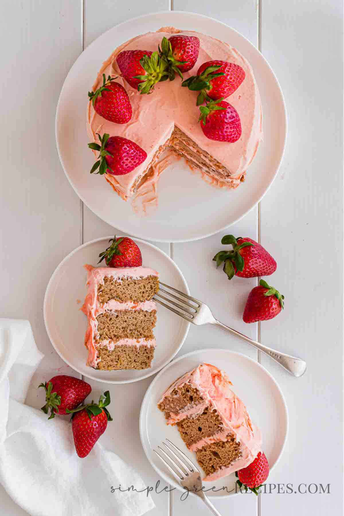 Cut Strawberry cake on a white plate, next to two slices of the cake on white plates.