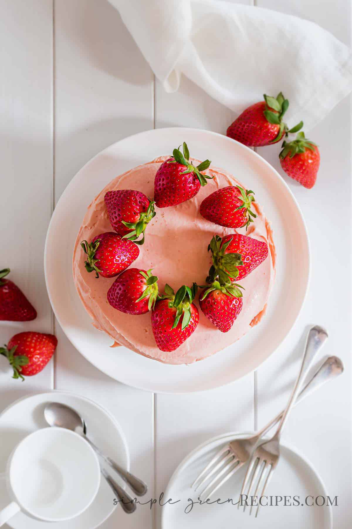 Strawberry cake on a white plate, topped with strawberries, next to dessert plates and coffee mugs.