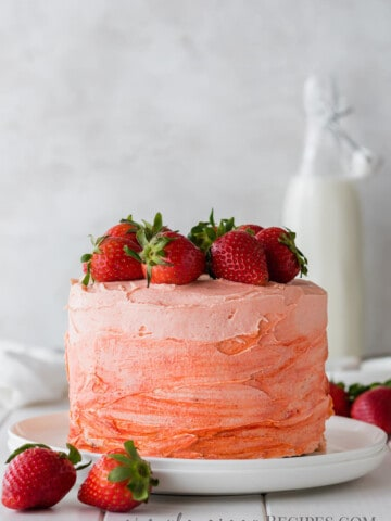 Strawberry cake on a white plate, topped with fresh strawberries
