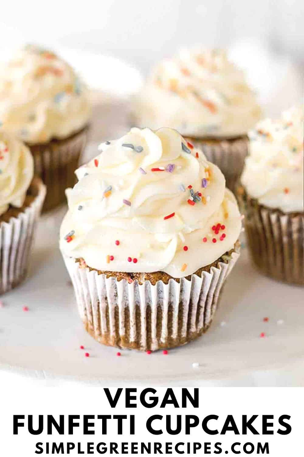 Cupcakes frosted with vanilla buttercream and topped with colourful sprinkles against a white surface