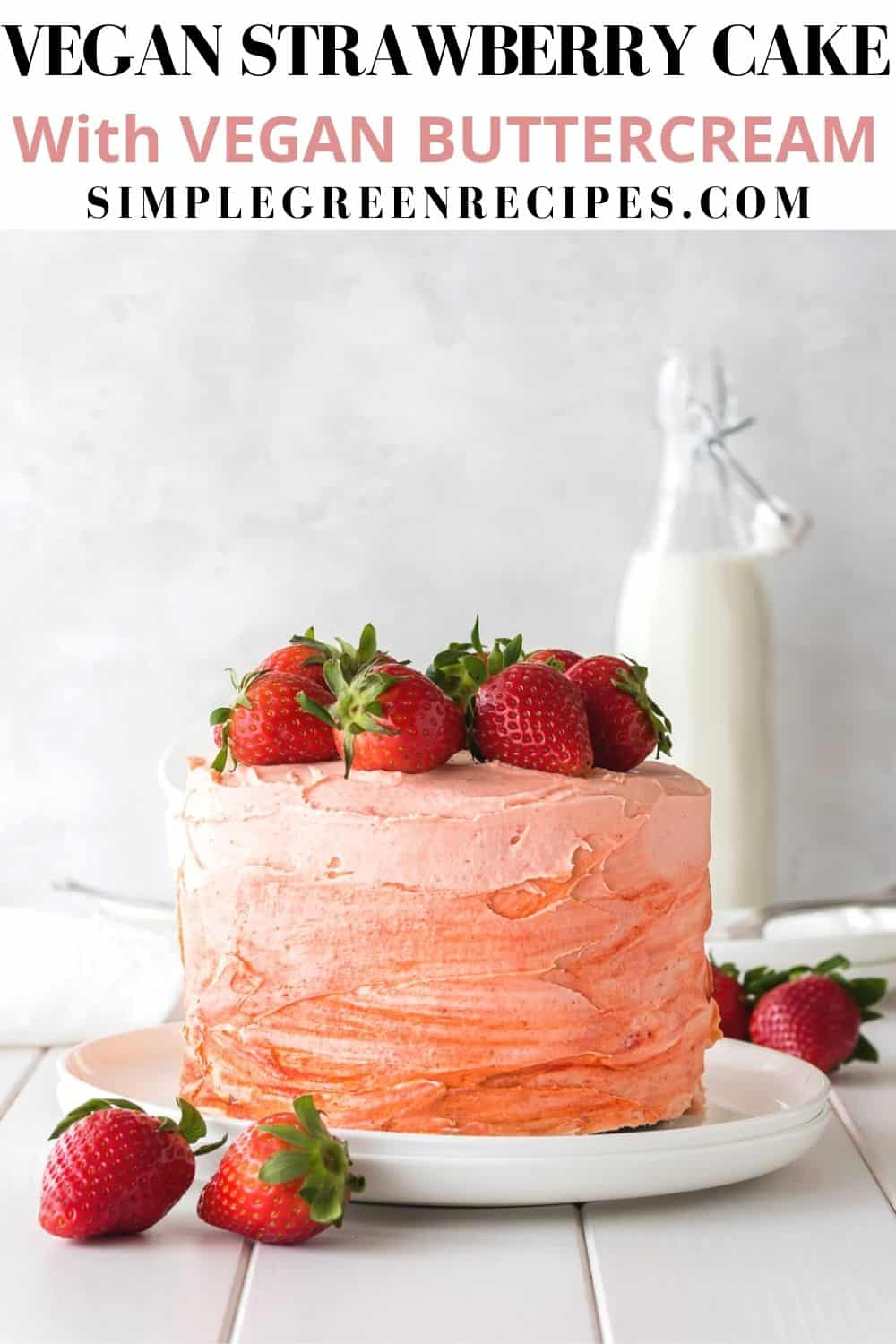 Strawberry cake on a white plate, topped with fresh strawberries, in front of a milk bottle.