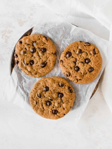 three chocolate chip cookies on a parchment paper