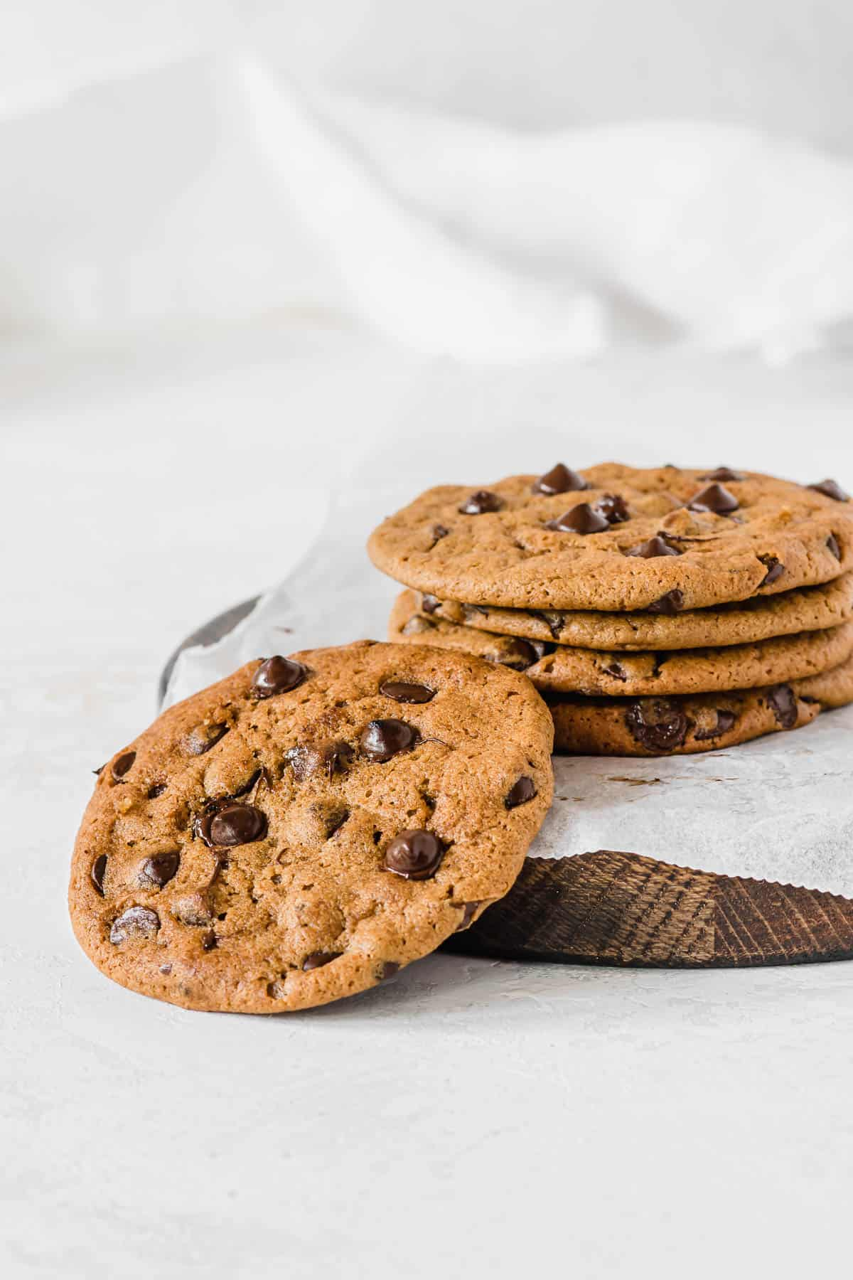 Stack of chocolate chip cookies on a parchment paper, over a round brown cutting board