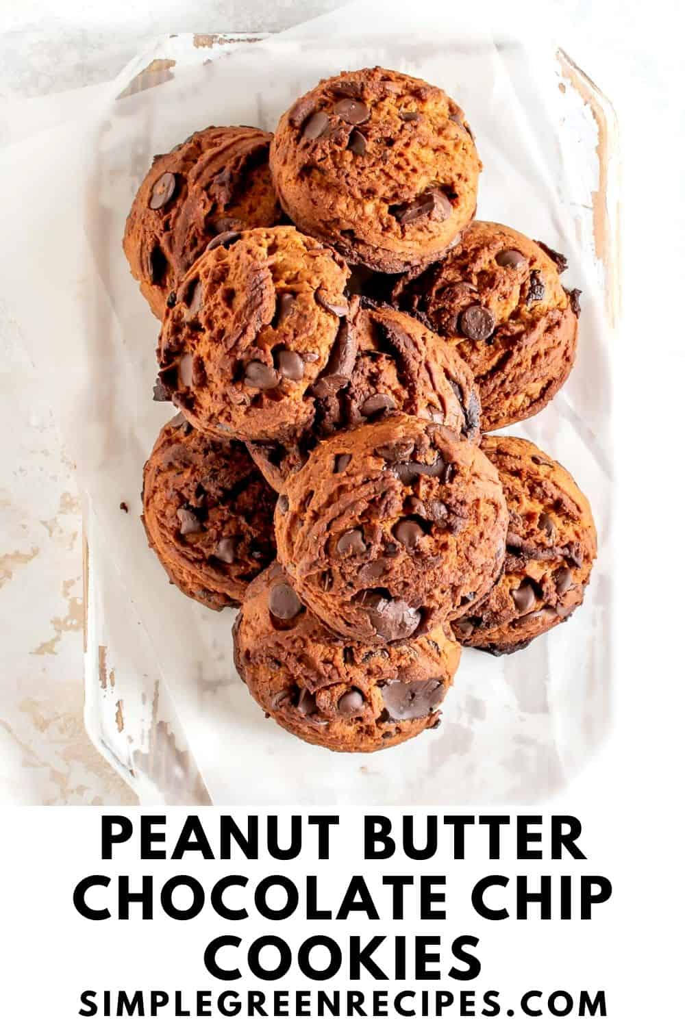 pile of peanut butter cookies with chocolate chips, on a white wooden cutting board