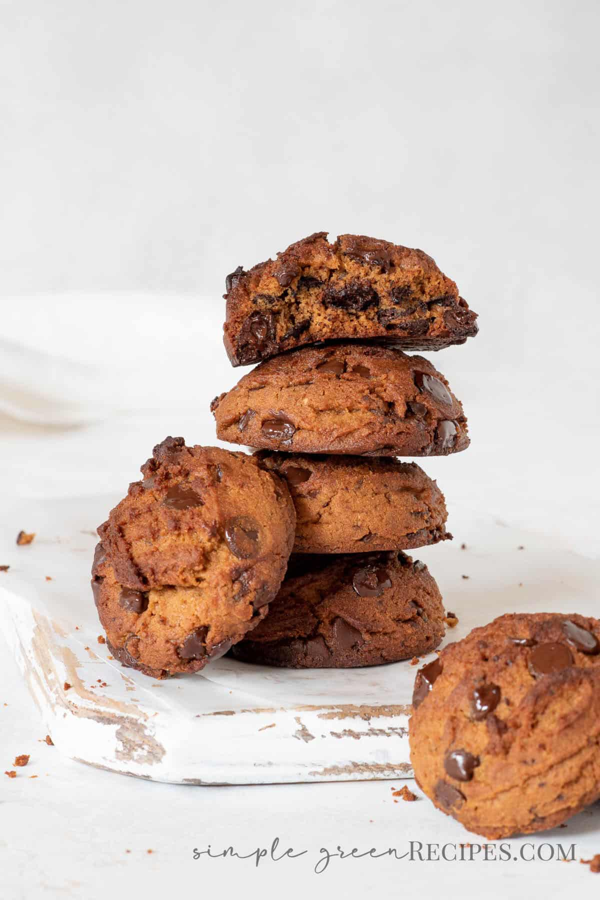 stack of peanut butter cookies with chocolate chips, on a white wooden cutting board