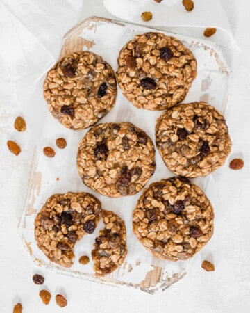 split vegan oatmeal cookie on a white board, surrounded by more cookies
