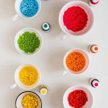 Seven white small bowls, with colorful homemade sprinkles, and the seven bottles of food coloring used.