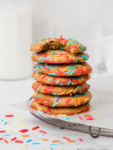 Stack of cookies with sprinkles on a parchment paper over a cooling rack