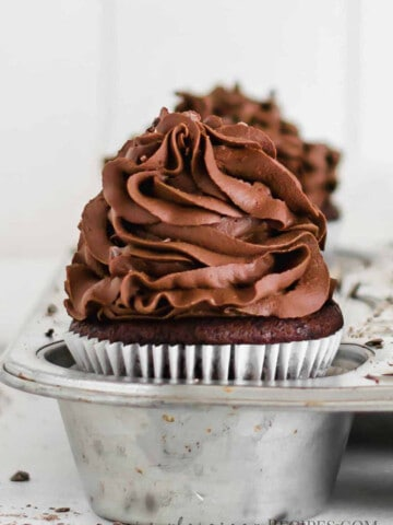 Chocolate cupcake frosted with chocolate frosting and placed in a muffin pan.