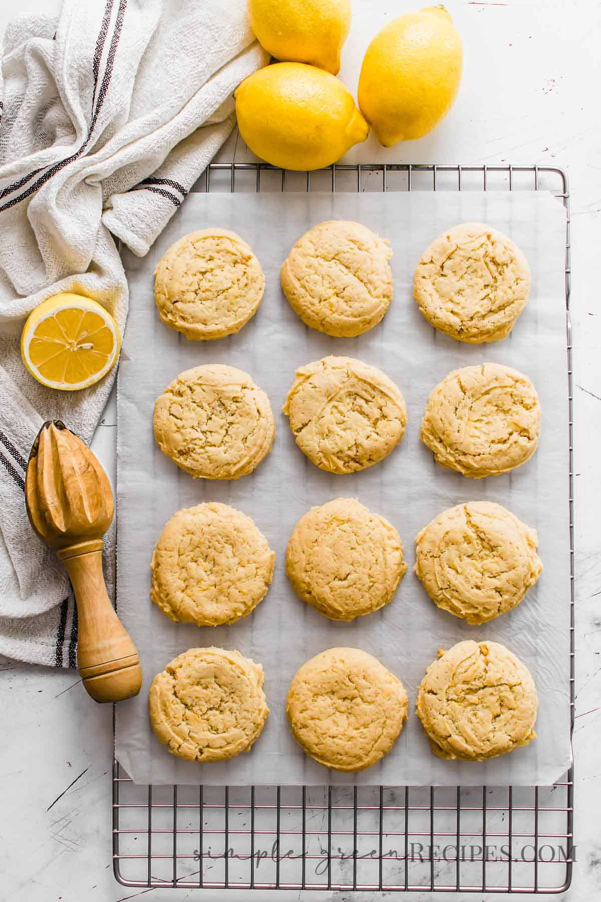 Cookies on a parchment paper over a cooling rack, surrounded by lemons, a dish towel and a wooden squeezer.