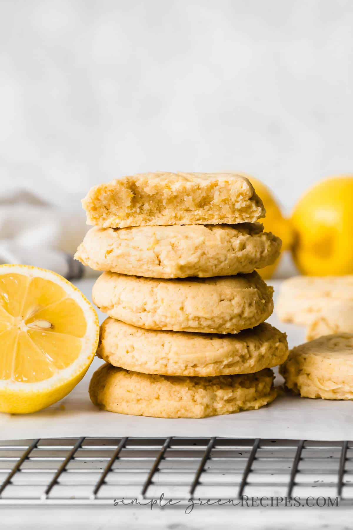 Stack of cookies next to a halved lemon, placed on a parchment paper over a cooling rack.